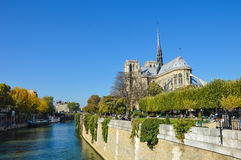 Notre Dame cathedral next to the river of Paris with boats and buildings summertime. River of Paris with boats and buildings summertime, France with the Royalty Free Stock Images