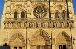 Notre Dame Cathedral, Paris, France. Gothic facade closeup with sunset light. Statues, rose window, archs and doors. royalty free stock photos