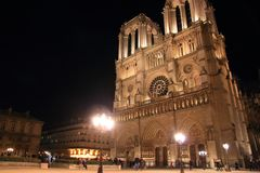 Notre Dame Cathedral in Paris and its lighting with tourists at night royalty free stock images