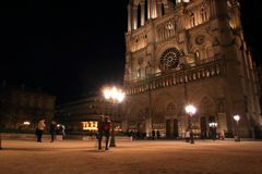 Notre Dame Cathedral in Paris and its lighting with tourists at night royalty free stock photography