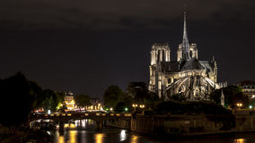 Notre Dame Cathedral in Paris at night. With Seine River along the way Royalty Free Stock Images