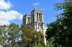 Notre Dame Cathedral from Seine river walk. Trees, towers and spire. Paris, France, blue sky with clouds. royalty free stock image