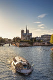 Notre Dame cathedral and sightseeing boat in Paris. Notre Dame cathedral and sightseeing boat on River Seine in Paris, France Stock Photo