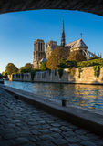Notre Dame cathedral at sunset and Seine River bank, Paris Royalty Free Stock Photography
