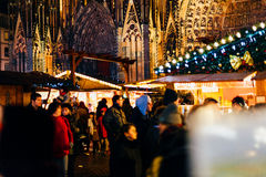 Notre-Dame cathedral with tourists and Christmas Market holidays. STRASBOURG, FRANCE - DEC 20, 2016: People walking between market stalls during Christmas Market Stock Photos