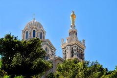 Notre-Dame-de-la-Garde in Marseille. Basilica Notre-Dame-de-la-Garde- of Marseille in France with trees in the foreground Royalty Free Stock Photo