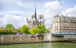 Notre Dame de Paris Catholic Christian Cathedral. With the Seine river, a bridge and typical parisian buildings on a sunny spring day Stock Image