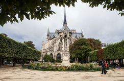 The Notre Dame de Paris church in a rainy day against the overcast sky and two people walking near the church and sharing one umbr Royalty Free Stock Image