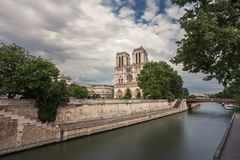 Notre-Dame de Paris, famous ancient catholic cathedral on the quay of the Seine river on a cloudy day. Touristic. Historical and architectural landmark in Royalty Free Stock Photography