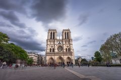Notre-Dame de Paris, famous ancient catholic cathedral on the quay of the Seine river on a cloudy day. Touristic. Historical and architectural landmark in Stock Photos