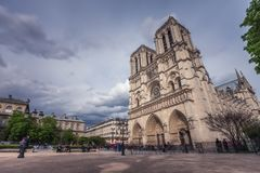 Notre-Dame de Paris, famous ancient catholic cathedral on the quay of the Seine river on a cloudy day. Touristic. Historical and architectural landmark in Royalty Free Stock Photos