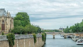 Notre Dame de Paris Garden on cite island timelapse, Paris, France. Park with green trees and flowers. View from Double bridge. River with boats. Cloudy sky at stock video footage