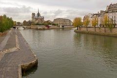 Notre Dame de Paris. Landmark and touristic spot: Gothic Notre Dame de Paris Cathedral on the the Seine river in Paris, France, by an autumn cloudy day with Stock Photos