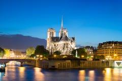 Notre Dame de Paris met cruise binnen schip op Zegenrivier bij nacht stock foto