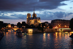Notre Dame de Paris by night. Sunset at Notre Dame De Paris from the bridge Pont de la Tournelle stock photos
