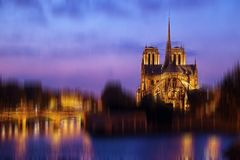 Notre Dame de Paris at night in blur motion. Notre Dame de Paris illuminated, with reflections in the river Seine. Motion blur filter applied Royalty Free Stock Photography