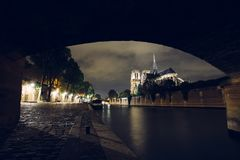 Notre-Dame de Paris by night. Famous ancient catholic cathedral on the quay of the Seine river and city lights. Reflection. Touristic historical and Stock Photos