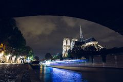 Notre-Dame de Paris by night. Famous ancient catholic cathedral on the quay of the Seine river and city lights. Reflection. Touristic historical and Royalty Free Stock Photos