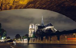 Notre-Dame de Paris by night. Famous ancient catholic cathedral on the quay of the Seine river and city lights. Reflection. Touristic historical and Stock Photography