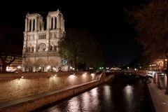 Notre Dame de Paris and the Seine. Notre Dame de Paris (France) Cathedral illuminated by night and a bridge over the Seine river stock images