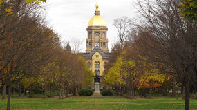 Notre Dame in the fall. The Golden Dome at the University of Notre Dame matches the colors of the remaining leaves on the trees in the fall royalty free stock photo