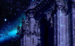 Notre-Dame of Paris. Inspired on Victor Hugo's novel, Quasimodo, at night, and looking at the shiny sky, stands on a gargoyle of the Notre-Dame cathedral of Royalty Free Stock Images
