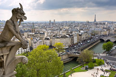 Notre Dame of Paris: Famous Chimera (demon) overlooking the Eiffel Tower at a spring day Royalty Free Stock Photography