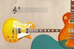 Notsystemet och två elektriska gitarrer för sunbursttappning och baksida av gitarr förkroppsligar på rätsidan av grov pappbakgrun Arkivbild