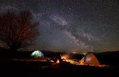Notte che si accampa in montagne Coppia le viandanti che hanno resto vicino a fuoco di accampamento, tenda turistica sotto il cie fotografia stock