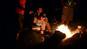 Notte dei ragazzi vicino a fuoco di accampamento archivi video