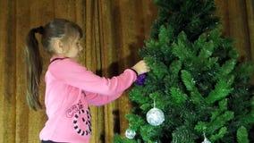 Notte di San Silvestro, Natale il bambino decora l'albero di Natale stock footage
