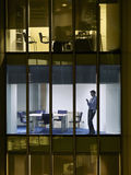 Notte di Text Messaging Late dell'uomo d'affari in ufficio Fotografie Stock Libere da Diritti