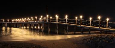 Notte e spiaggia di sabbia di estate romantica con il pilastro illuminato Fotografia Stock