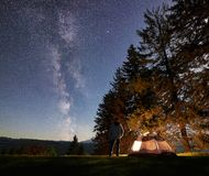 Notte maschio del enjoyng della viandante che si accampa vicino alla tenda turistica al fuoco di accampamento in corso il cielo e fotografia stock