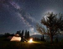 Notte maschio del enjoyng della viandante che si accampa vicino alla tenda turistica al fuoco di accampamento in corso il cielo e fotografia stock libera da diritti
