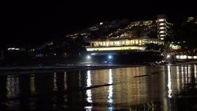 Notte sulla spiaggia sui precedenti dell'hotel spiaggia con le luci notturne della città archivi video