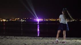 Notte, una ragazza teenager in una gonna brillante sta ballando, vista dalla parte posteriore contro le luci della città d'ardore video d archivio