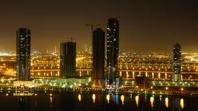 Notte veduta delle città della Doubai e della Sharjah su un lago Immagine Stock Libera da Diritti