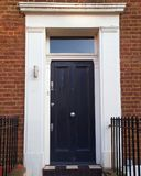 Notting hill, London, grunge entrance black door. On brown brick wall background Royalty Free Stock Photo