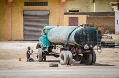 Nouakchott, Mauritanie - 8 octobre 2013 : Scène de rue de pneu changeant d'homme non identifié sur le vieux camion de l'eau photographie stock libre de droits