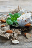 Nougat with almonds and candied fruit on a bronze plate. Stock Photos