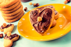 Nougat cream on cookies. Sweet nougat cream on the heart shape cookies.Selective focus on the big right cookie Stock Photography