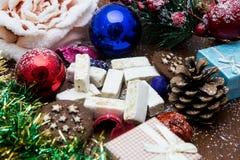 Nougat, doce espanhol tradicional para o Natal fundo escuro do nougat da amêndoa doce com as decorações da neve e do abeto Fotografia de Stock Royalty Free