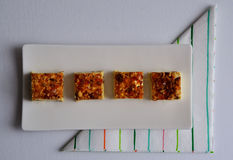 Nougat. Pieces of nougat lined up on a rectangular plate. Also a nice colored napkin Royalty Free Stock Photos