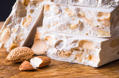 Nougat on torrone. Nougat or torrone with nuts christmas sweets on rustic wood background Royalty Free Stock Photography