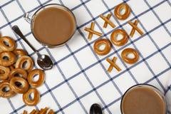Noughts και σταυροί που χρησιμοποιούν μπισκότα και δύο φλιτζάνια του καφέ στοκ εικόνες