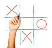 Noughts and crosses. A close up of a female hand playing noughts and crosses over white background Royalty Free Stock Photography