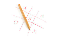 Noughts and crosses game. Red pencil with noughts and crosses game on white paper Royalty Free Stock Image