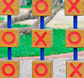 Noughts and crosses in the park. Wooden tic tac toe in a green park Royalty Free Stock Image