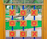 Noughts and crosses in the park. Wooden tic tac toe in a green park Royalty Free Stock Images